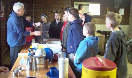 Our Scoutmaster instructing Scouts on the proper care of cast iron cookware, Canyon Camp February 2003.  